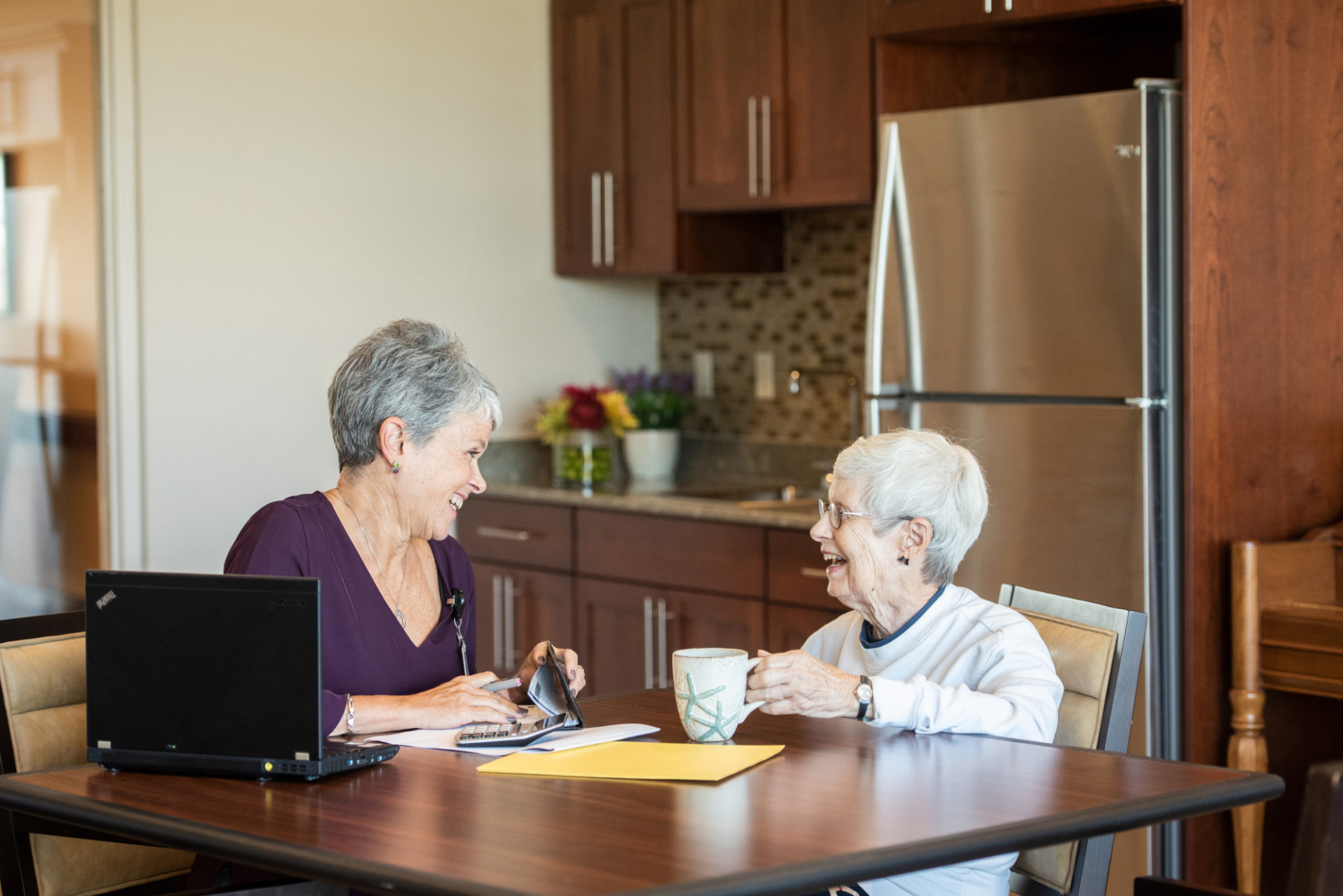 two seniors talking at kitchen table
