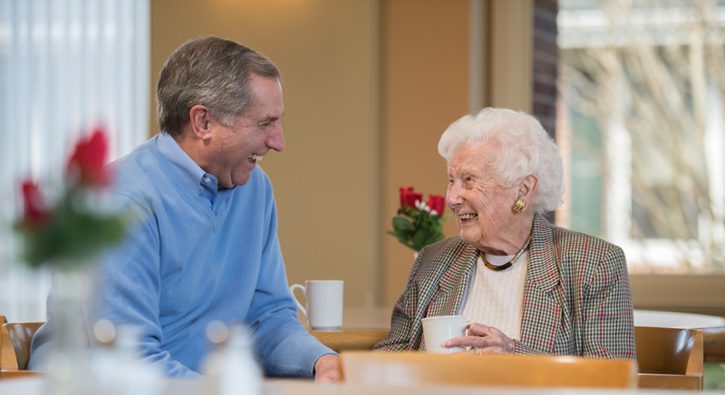 two seniors talking over coffee