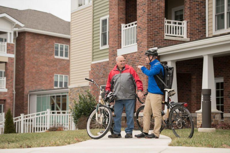 two men talking by their bikes